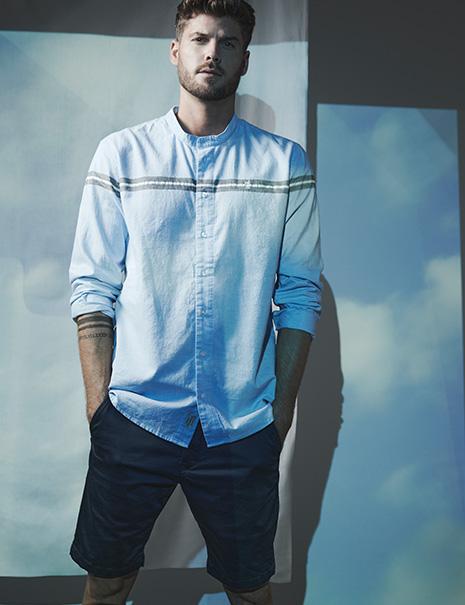 Mann in blauen Shorts und hellblauem Hemd