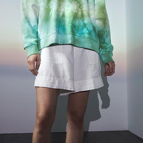 Frau in weißen Shorts und grünem Sweatshirt