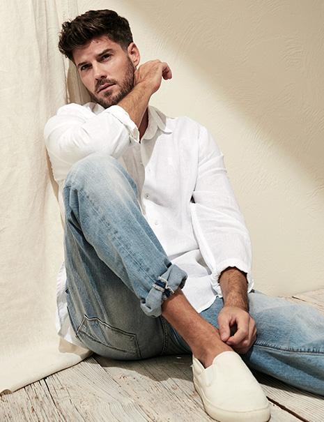 Mann in hellblauer Jeans und weißem Leinenhemd
