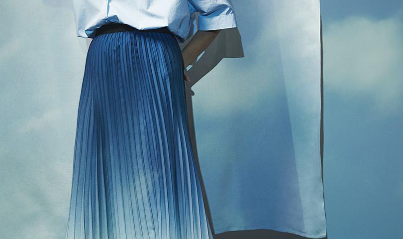 Frau in blauem Plisseerock